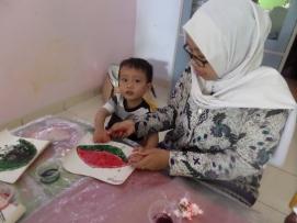 Raditya dan Ms. Nor asyik mengerjakan Finger Painting