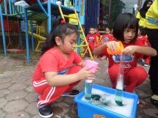 Kakak TK B sudah pandai menuang air ke wadah plastik